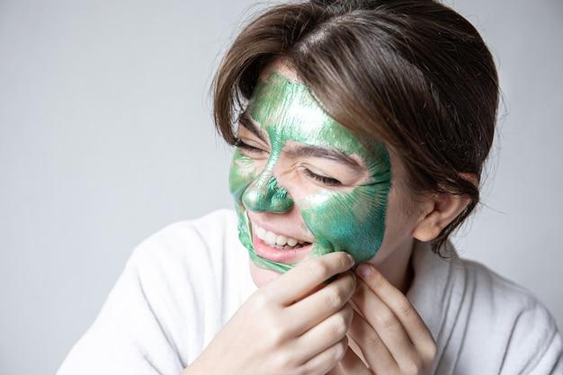 Retrait d'un masque cosmétique vert du visage de jolie fille