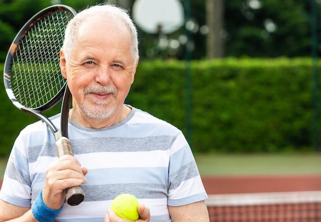Un retraité actif, portrait d'homme senior jouant au tennis à l'extérieur, sports à la retraite, concept sportif