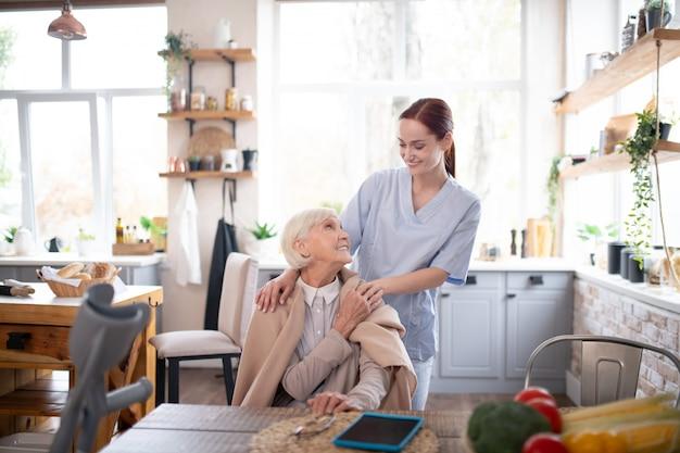 Retraité âgée se sentant reconnaissante envers son aimable soignant