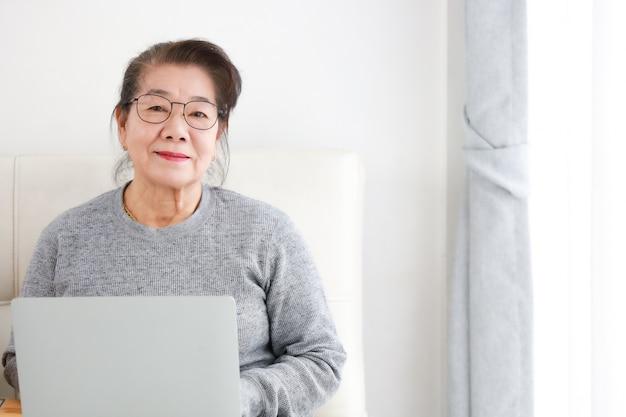 Retraite asiatique femme senior à l'aide d'un ordinateur portable dans le salon