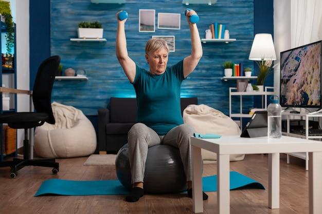 Retraité ciblé assis sur ballon suisse de remise en forme levant la main étirant le muscle du bras