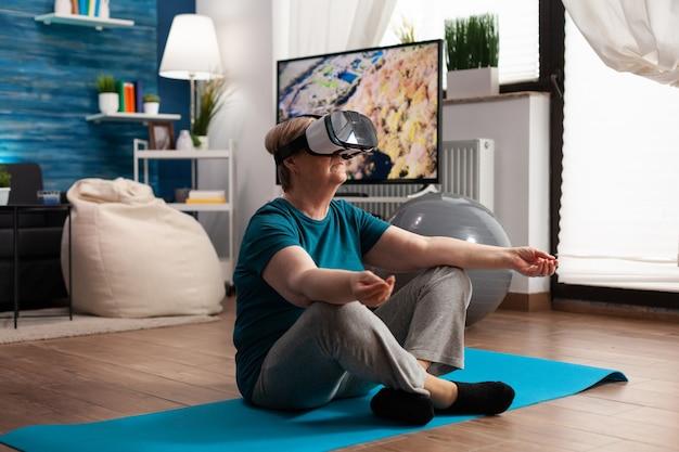 Retraite une femme âgée assise sur un tapis de yoga en position du lotus dans le salon portant un casque de réalité virtuelle pendant l'entraînement de méditation pilates