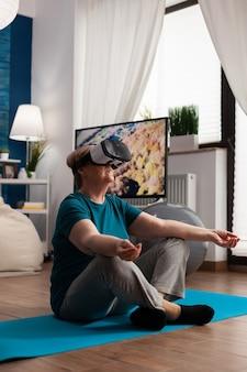 Retraite femme âgée assise sur un tapis de yoga en position du lotus dans le salon portant la réalité virtuelle