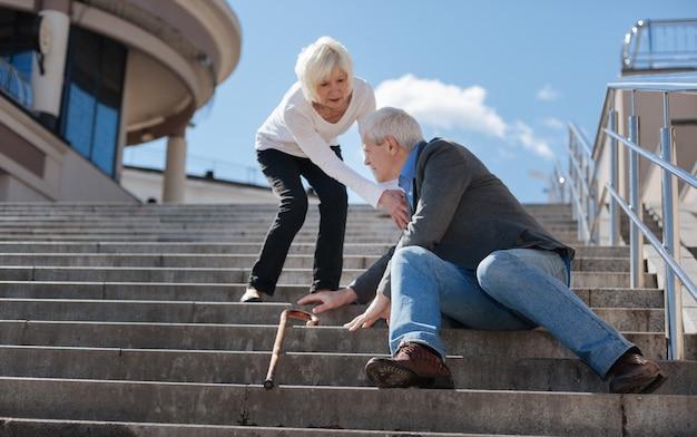 Retraité inquiet frustré aux cheveux blancs assis dans la rue et ayant le vertige alors qu'il n'est pas indifférent femme l'aidant
