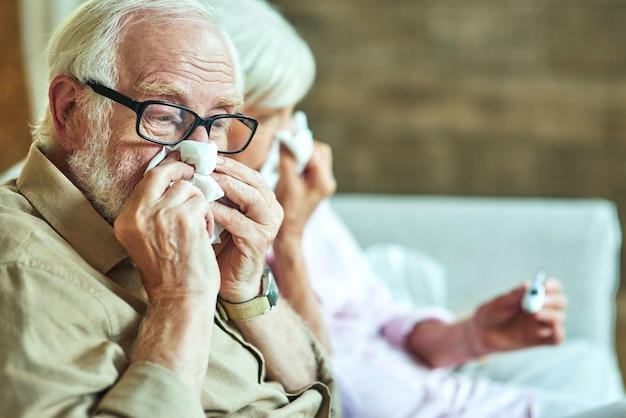Retraité masculin utilisant des serviettes en papier pour un rhume