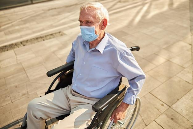 Retraité en masque handicapé marchant en fauteuil roulant