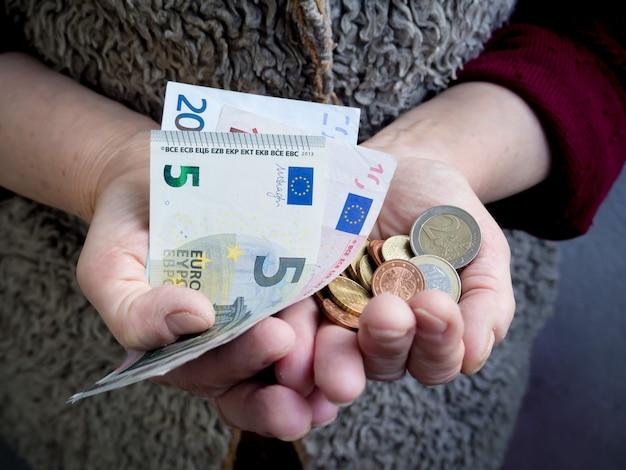 Retraité avec des pièces en euros en main. le problème de la pauvreté.