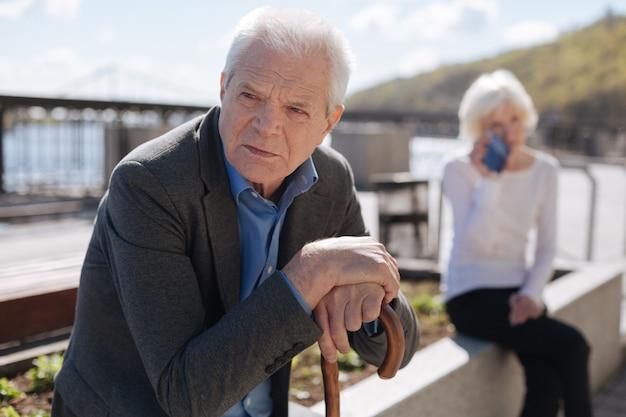 Retraité san perplexe âgé ses mains sur le bâton et regardant loin devant tandis que malheureuse femme se sentant déprimée
