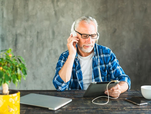 Retraité senior homme écoute de la musique à travers le casque sur la tablette