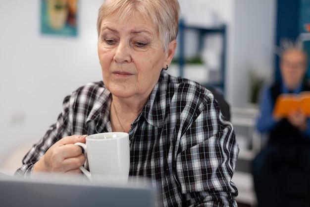 Retraité senior avec une tasse de café dans les mains en lisant les nouvelles du matin