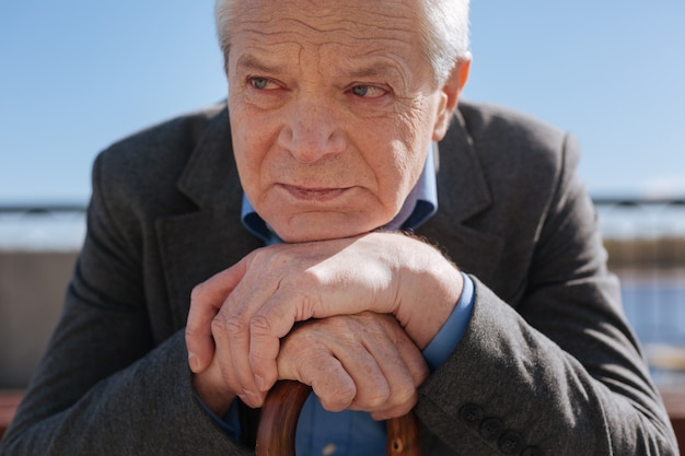 Un retraité soigné et perplexe bouleversé mettant ses mains sur le bâton et jugeant la nouvelle génération alors qu'il était assis sur le banc