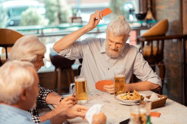 Les retraités jouent aux cartes. retraités positifs aux cheveux gris jouant aux cartes et buvant