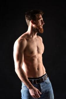 Retrato de hombre sin camisa y con el fondo negro.