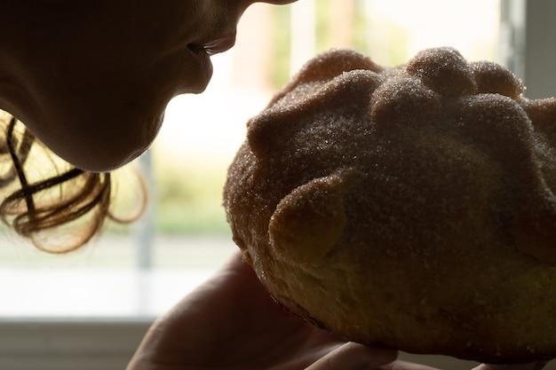 Rétro-éclairage de femme sentant le pan de muerto mexicain traditionnel, espace de copie