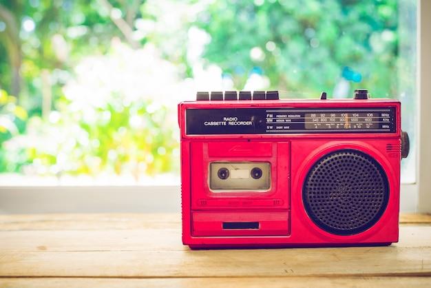 Rétro radio couleur rouge sur table avec fond de la nature, filtre de couleur vintage