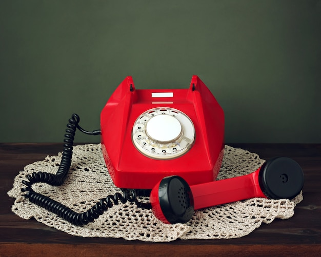 Rétro téléphone rotatif rétro avec le récepteur pris sur une serviette en dentelle