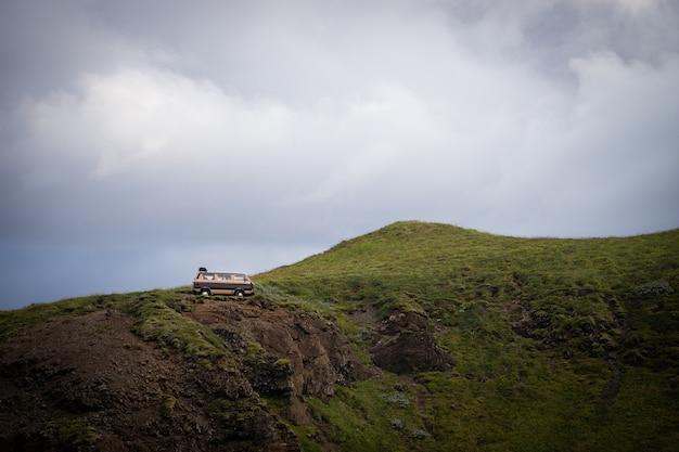 Retro van stationné dangereusement sur le bord de la falaise. concept d'aventure, de liberté et de voyage.