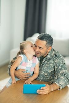 Retrouvailles à la maison. heureux père et fille réunis à la maison et regardant des dessins animés ensemble