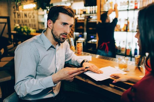 Une réunion d'affaires de deux personnes dans un bar. l'homme explique quelque chose à la femme. elle l'écoute très précis et prudent. barman se tient non loin d'eux.