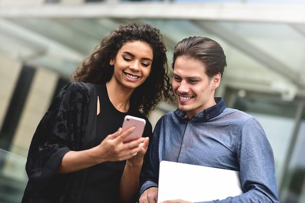 Réunion d'affaires homme et femme discutant du travail et regardant l'écran du smartphone travailler ensemble