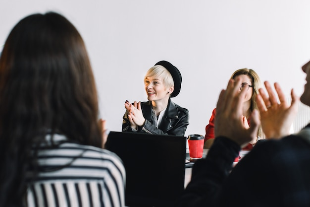 Réunion de l'agence créative - groupe de gens d'affaires en tenue décontractée parlant pendant la conférence au bureau et applaudissant pendant le discours