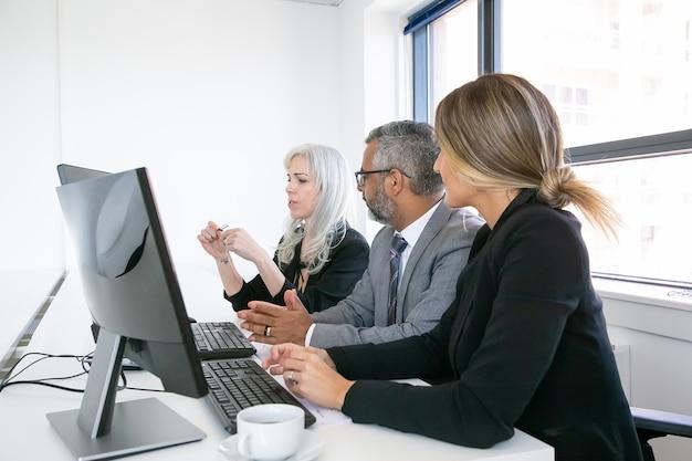 Réunion des chefs d'entreprise. équipe de professionnels assis sur le lieu de travail avec des moniteurs ensemble et discutant du projet. vue de côté. concept de réunion d'affaires