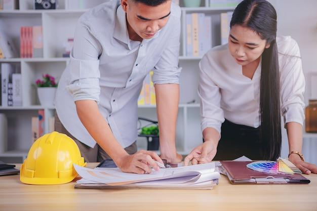 Réunion de concepteur d'architecte d'équipe et graphique de travail avec le nuancier et le matériel assortis