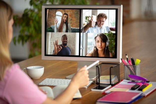 Réunion à distance. femme travaillant à domicile pendant le coronavirus ou la quarantaine covid-19, concept de bureau à distance. jeune patron, responsable devant le moniteur lors d'une conférence en ligne avec des collègues et une équipe.