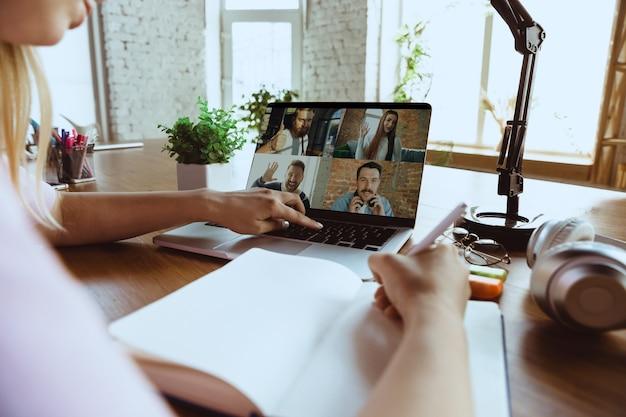 Réunion à distance. femme travaillant à domicile pendant le coronavirus ou la quarantaine covid-19, concept de bureau à distance. jeune patron, responsable devant un ordinateur portable lors d'une conférence en ligne avec des collègues et une équipe.