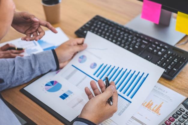 Réunion de l'équipe d'affaires travaillant avec le nouveau projet de démarrage, discussion et analyse de données, tableaux et graphiques, utilisation d'un ordinateur