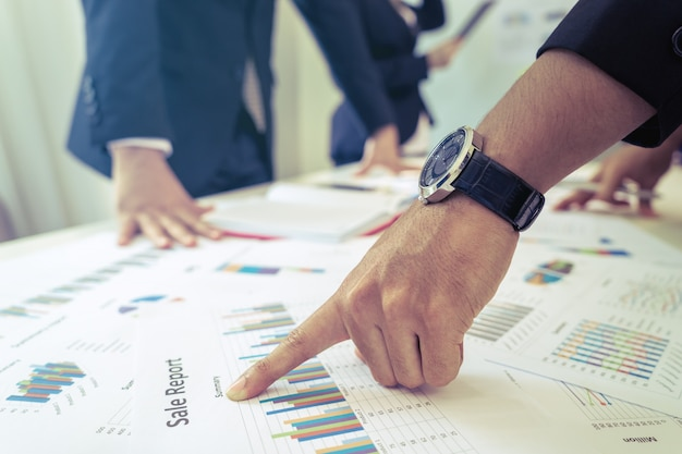 Une réunion de l'équipe de gestion discute d'un graphique de données sur la table