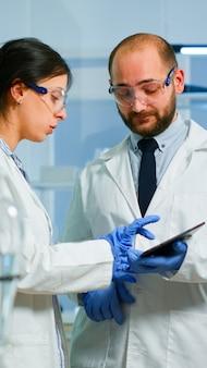 Réunion de l'équipe scientifique et discussion des résultats du traitement debout dans un laboratoire de recherche pointant sur une tablette. trucs examinant le développement d'un vaccin contre le virus covid19 en utilisant la haute technologie pour la recherche.