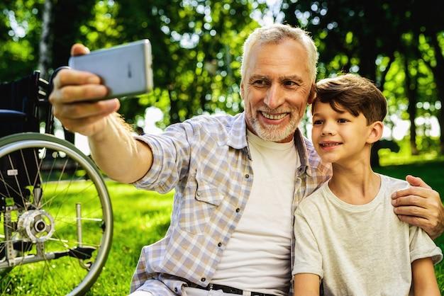 Réunion de famille dans le parc. petit garçon et grand-père selfie.