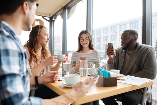 Réunion de fin de semaine. portrait de jeunes internationaux passent leur temps commun ensemble à la cafétéria en ayant une conversation agréable.