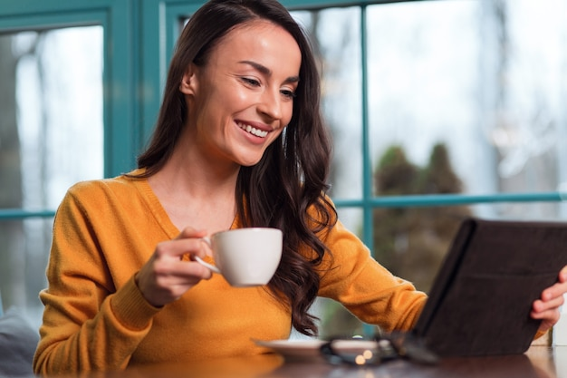 Réunion en ligne. jolie jeune femme enthousiaste, appréciant le thé tout en utilisant la tablette et souriant