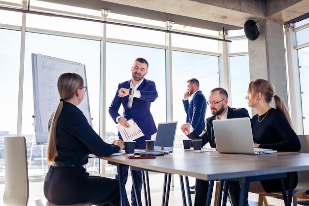 Réunion réussie de gens d'affaires, discutant de nouvelles idées commerciales, utilisant des diagrammes, assis ensemble. arrière-plan de bureau moderne. rencontre des partenaires commerciaux à la conférence sur le développement des affaires