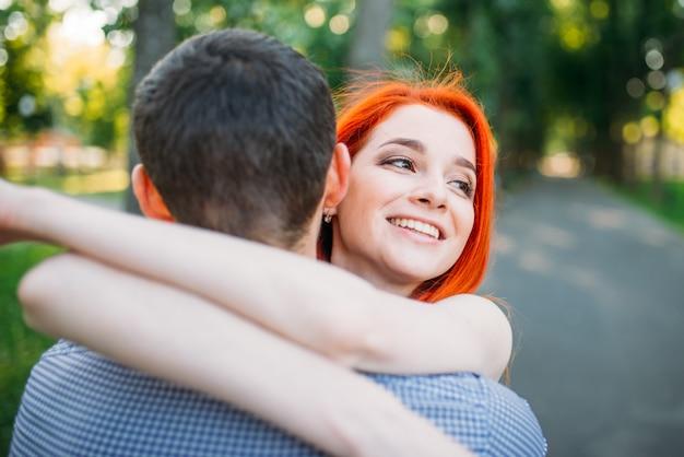 Réunion romantique, jeune couple étreint ensemble dans le parc d'été vert. loisirs homme et femme en plein air