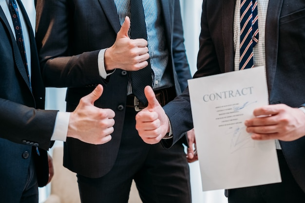 La réussite des entreprises. les hommes en costumes gesticulant pouces vers le haut