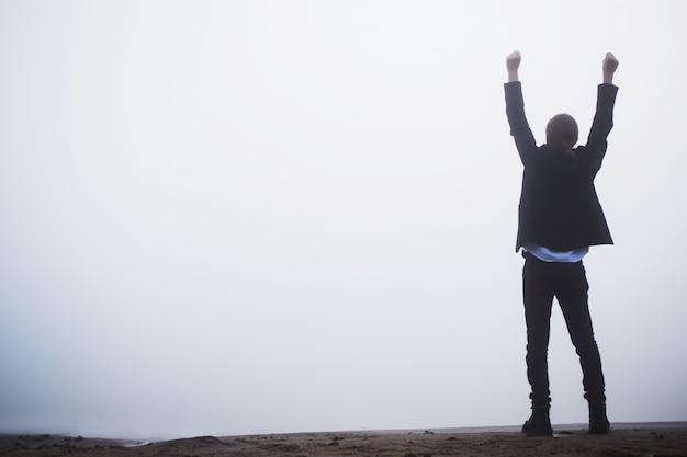 La réussite des entreprises. silhouette d'homme heureux sur fond de brouillard. homme réussi lever la main contre l'aube. silhouette en capuche. concept de vie avec figure dans le capot. succès de la vie. gagnez le concours. concept de triomphe