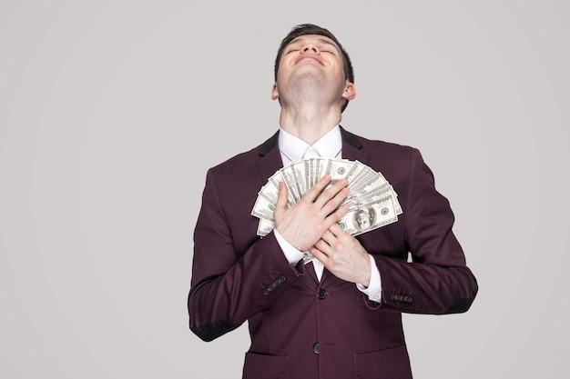 Le rêve devient réalité! jeune homme d'affaires satisfait en manteau violet classique debout, fier les yeux fermés et s'appuyer sur un ventilateur d'argent à la poitrine et sourire. studio intérieur tourné, isolé, fond gris