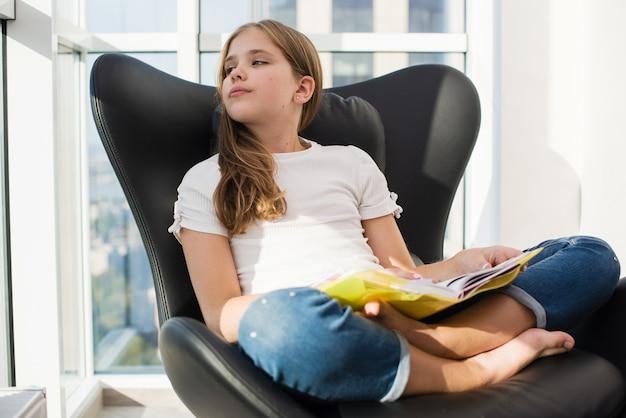 Rêve d'une étudiante préadolescente avec un livre de lecture en couverture jaune, assise dans une pose de lotus sur une chaise en cuir noir avec intérieur de fenêtres panoramiques, portant un jean pieds nus