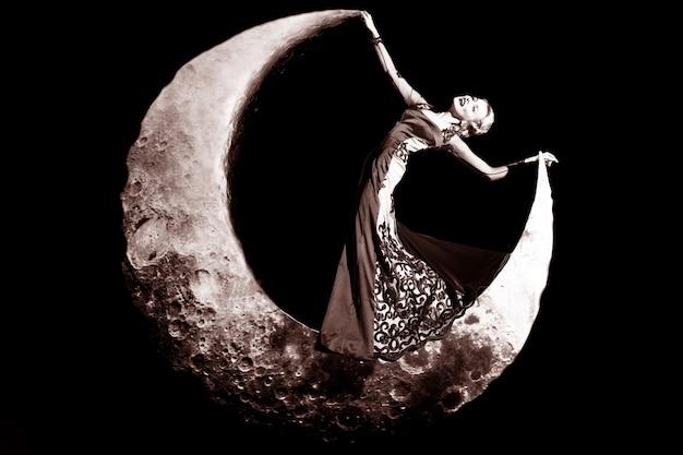 Rêve de mode. belle jeune femme rétro posant sur la lune en robe élégante de soirée.
