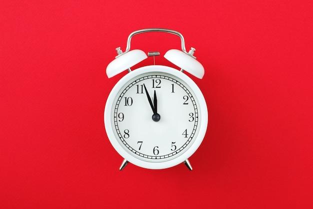 Réveil affichant cinq minutes à douze sur fond rouge
