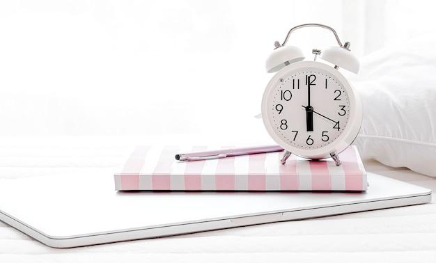 Réveil et agenda sur un ordinateur portable dans la chambre