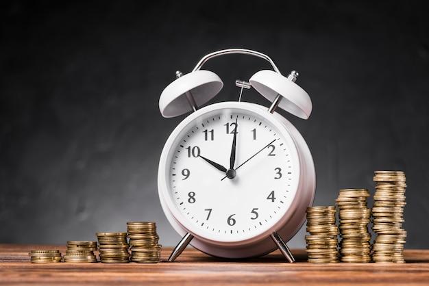 Réveil blanc entre la pile croissante de pièces de monnaie sur une table en bois sur fond gris