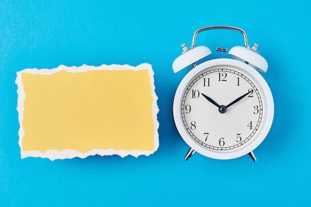 Réveil blanc et feuille de papier déchiré vide sur fond bleu