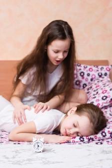 Réveil blanc et une fille essayant de réveiller une autre fille