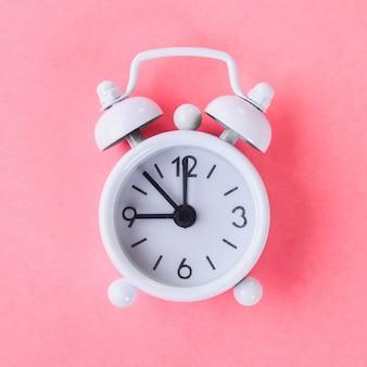 Réveil blanc sur fond bleu et rose pastel.