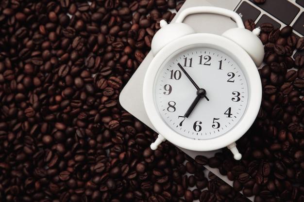 Réveil blanc et grains de café sur clavier