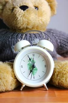 Réveil blanc style vintage devant ours en peluche